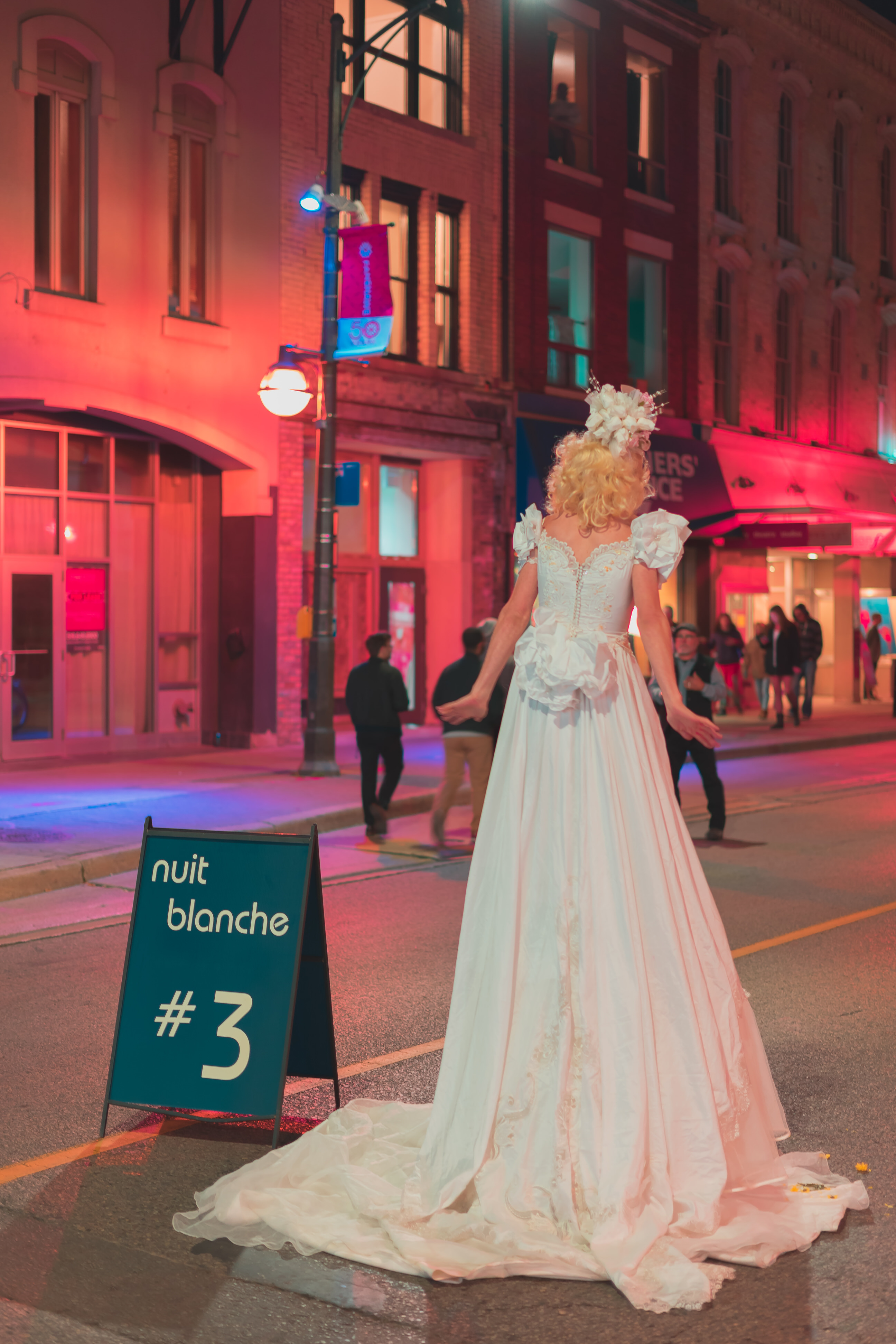Shot from behind tall bride performing at Nuit Blanche in London